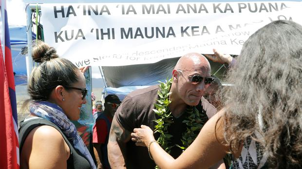 "Actor Dwayne ""The Rock"" Johnson visits with kupuna, an honoured elder, during a visit to the protest site blocking the construction of the TMT telescope (Jamm Aquino/Honolulu Star-Advertiser/AP)"