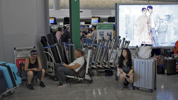 Stranded travellers wait in the departure hall of the Hong Kong International Airport (Vincent Thian/AP)
