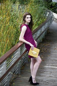 Leaving Cert student Abby wears wears a plum coloured textured shift dress, Victoria by Victoria Beckham (€585), Kurt Geiger Heels (€120), Ted Baker (€100) and mustard yellow box clutch with metallic clasp, Sophie Hulme (€43)
