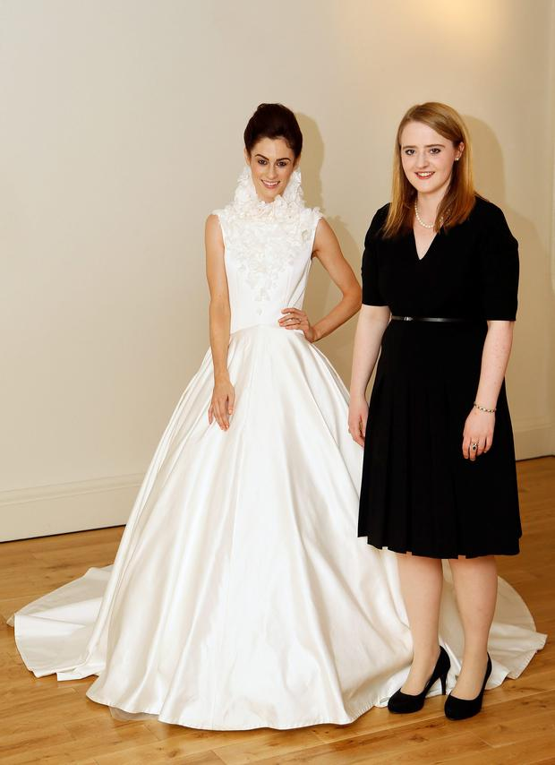 Madeline Mulqueen models the tailored bridal gown designed by student Jennifer Young (right), who won the 'excellence in craftsmanship' award at the National Tailoring Academy in Dublin
