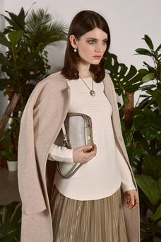 Pale camel edge-to-edge coat, €279.95, In Wear; White cotton ribbed jumper, €89.95, metallic pleated skirt, €99.95, Oui; Necklace, €39, Absolute Jewellery Metallic chain handle bag, €95, Guess