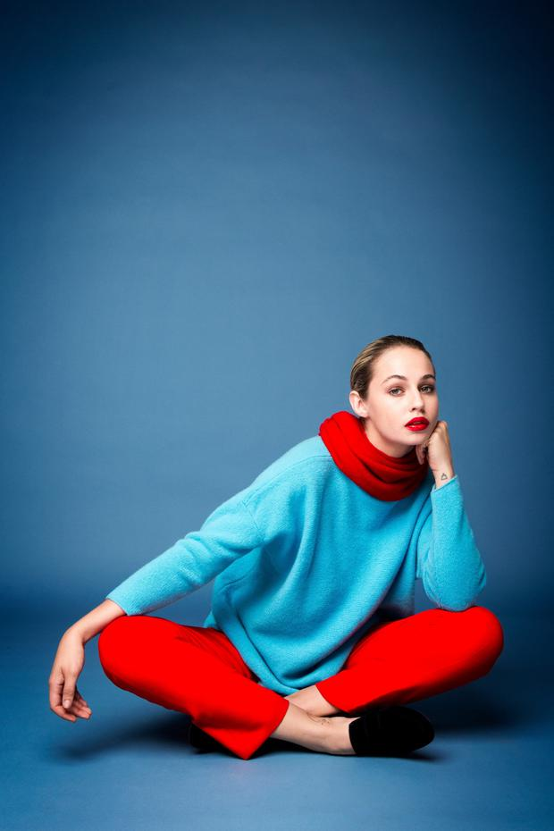 Model Thalia Heffernan wears a red merino knit scarf, €120; turquoise merino knit sweater, €225, and 'Jill' pants in red, €210