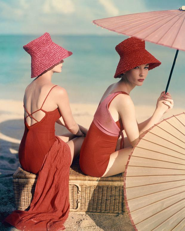 Two models seated on a wicker basket at the beach, published in Vogue in 1959