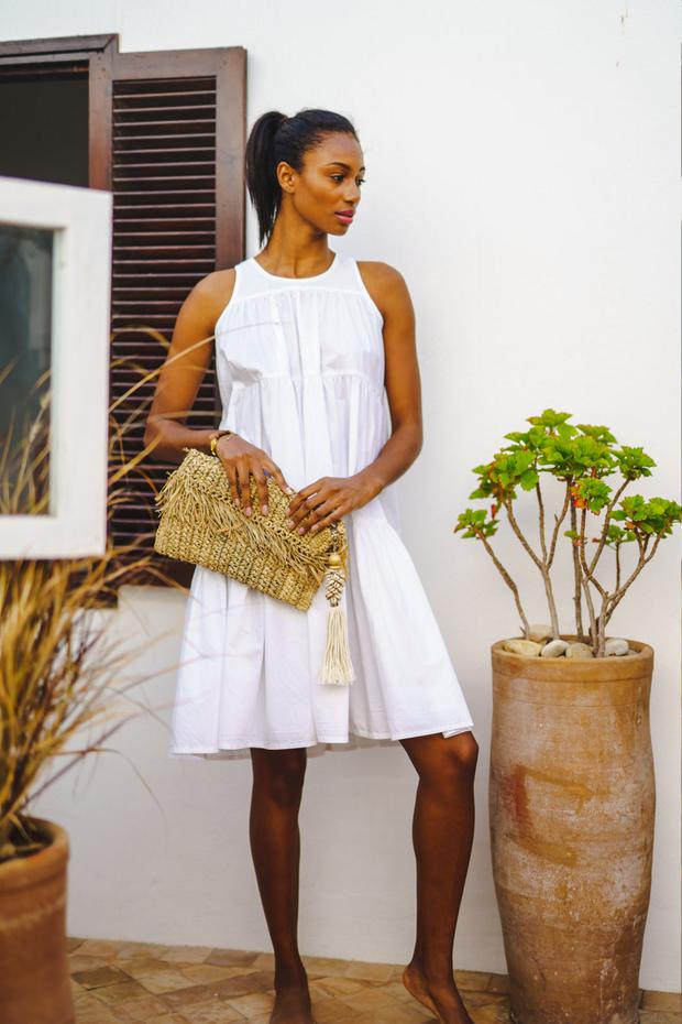 Plain white cotton tier dress, €182; 'Bo' tassel clutch, €135