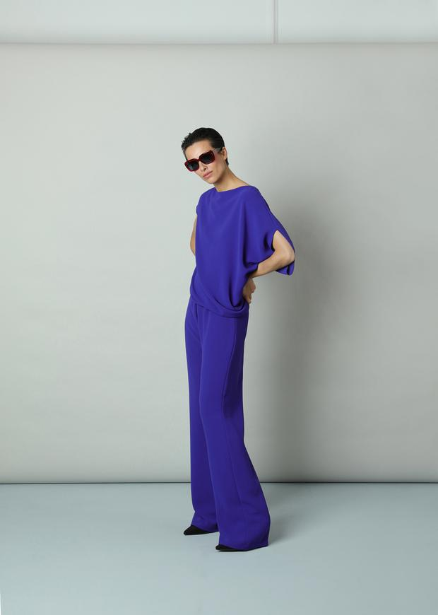 'Ruby' purple jumpsuit woven crepe, €479; 'Maeve' fuchsia sunglasses, €350, from the Wolfhound Eyewear range available at Optica, Dawson Street, Dublin; black sock boots, €150, by Marian at Arnotts, Henry Street, Dublin 1