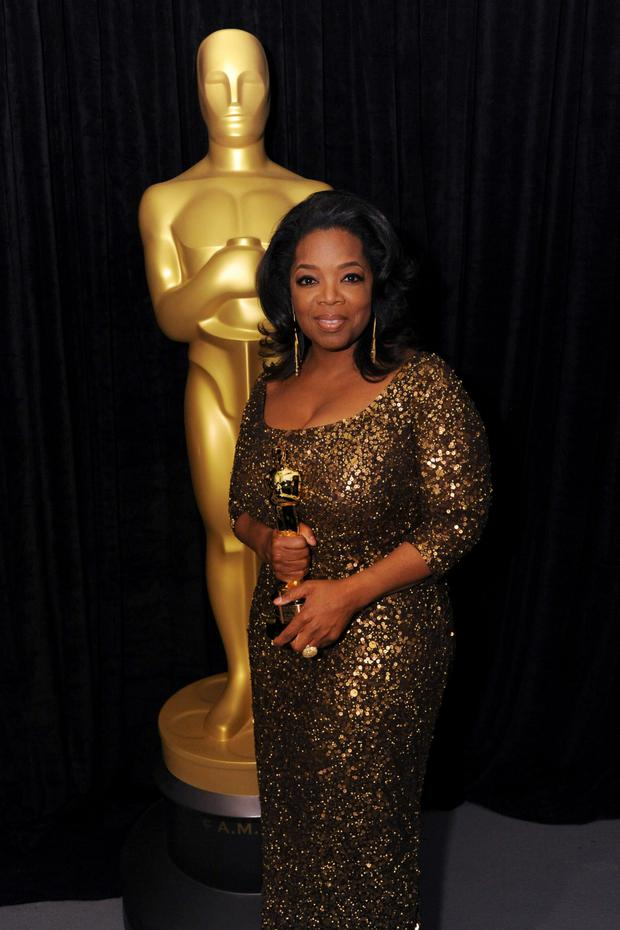 Oprah Winfrey wearing a Theia gold sequinned dress when she received an honorary Oscar in 2011