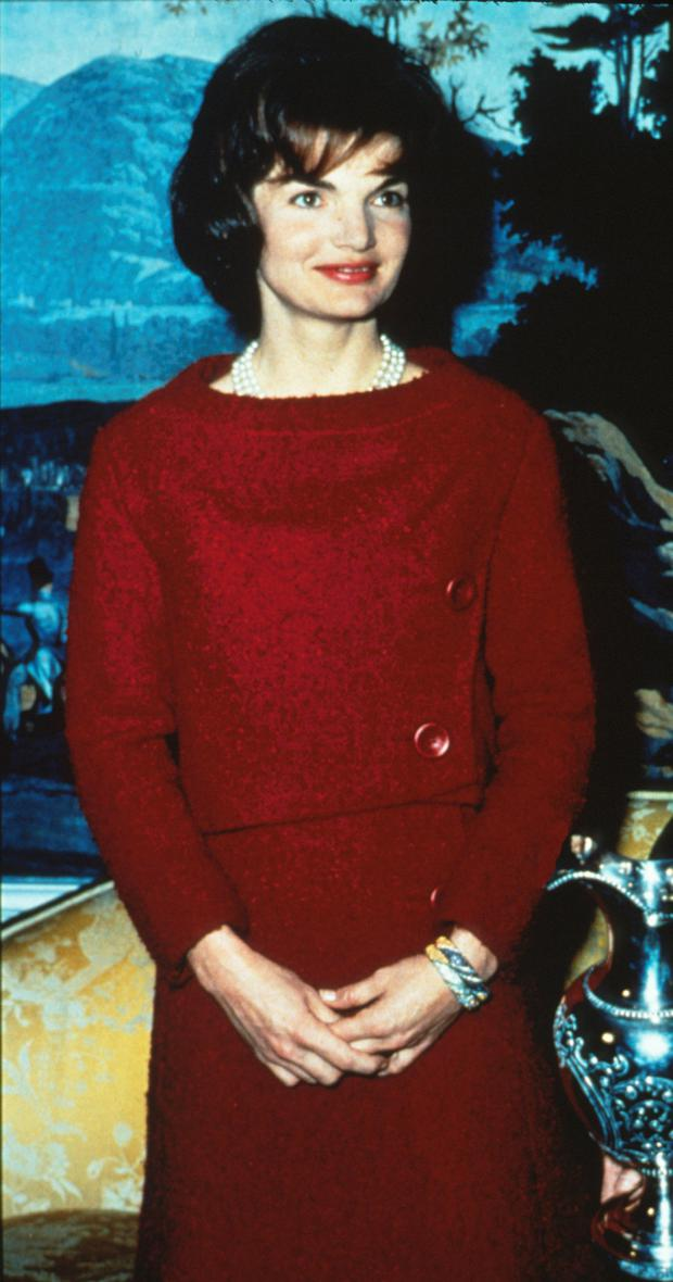 The lady in red: Jackie Kennedy giving a White House tour