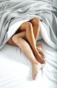 Couple tangled in the sheets