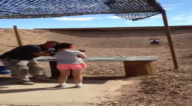 Charles Vacca instructs the nine-year-old girl at the Last Stop shooting range in White Hills, Arizona, just before the accident happened. Photo: Reuters