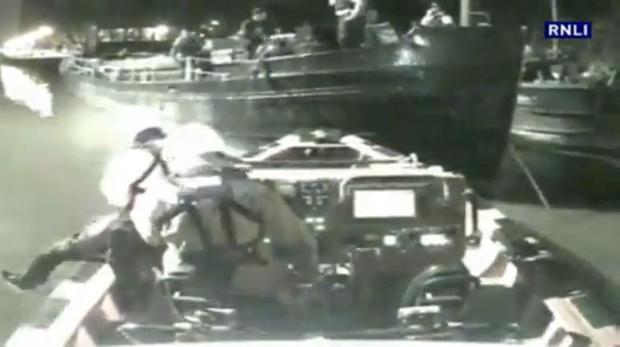 Crew are seen lifting the frozen man from the water to the left of the picture