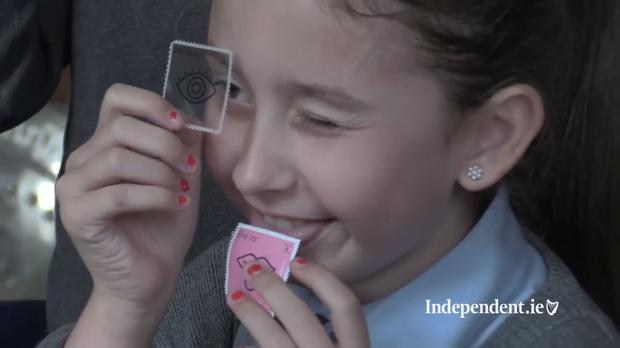 Tamzin Kelly (9) giving An Post's new strawberry-flavour stamp the taste test