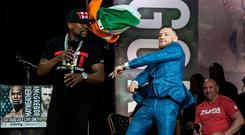 Conor McGregor, right, throws an Irish flag at Floyd Mayweather during a promotional stop in Toronto on Wednesday, July 12, 2017, for their upcoming boxing match in Las Vegas. (Christopher Katsarov/The Canadian Press via AP)