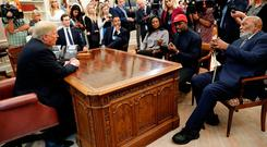 U.S. President Donald Trump listens as rapper Kanye West speaks during a meeting with NFL Hall of Fame player Jim Brown (R) and others in the Oval Office at the White House in Washington, U.S., October 11, 2018. REUTERS/Kevin Lamarque