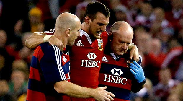 Sam Warburton (C) is assisted from the field during their rugby union test match