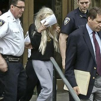 In an image made from video, actress Amanda Bynes, centre, is escorted after a Manhattan criminal court appearance (AP/APTN)
