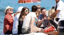 Bono arrives at St Tropez's exclusive Club 55 by boat, joined by friends and his daughter Eve.