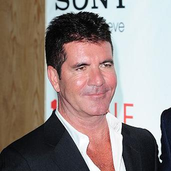 Simon Cowell has been told off by police for bringing his dogs to the beach in Miami