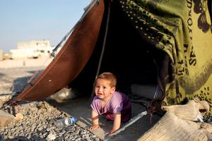 A Syrian refugee child plays in front of their makeshift shelter near a truck close to the Turkish border post of Akcakale, province of Sanliurfa, earlier this week