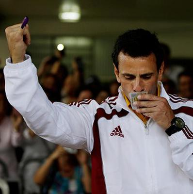 Opposition presidential candidate Henrique Capriles kisses his identification card as he holds up his inked finger after voting (AP/Fernando Llano)