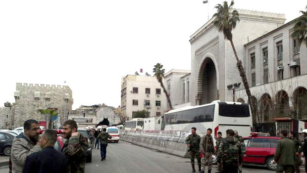 Syrian security forces gather in front the main judicial building in Damascus (SANA/AP)
