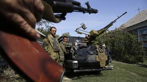Pro-Russian rebels stand next to their car with a heavy machine gun in Donetsk, eastern Ukraine (AP)