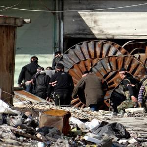 This citizen journalism image shows members of the free Syrian Army hiding behind scrap metal during an attack against Syrian government forces (AP Photo)