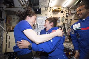 Christina H. Koch, left, and Jessica Meir greet each other after Ms Meir's arrival on the International Space Station (Nasa/AP)