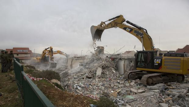 Bulldozers demolish houses in the West Bank settlement of Ofra (AP)