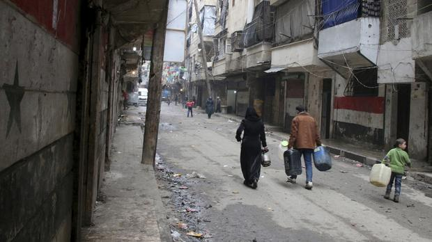 Civilians look for fuel and water in the ravaged city of Aleppo (AP)