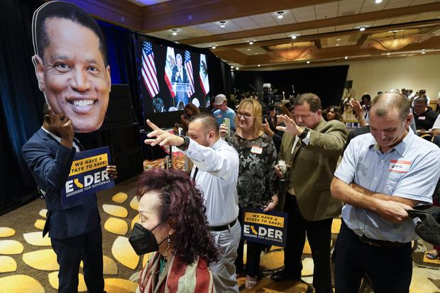 Supporters of Republican conservative radio show host Larry Elder pray while a man holds up a cut-out of Mr Elder's face at a gathering as polls closed for the California gubernatorial recall on Tuesday (Ashley Landis/AP)