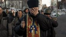 A priest is overcome with emotion as he holds a memorial service for protesters killed during clashes with the police in Kiev (AP)