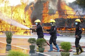 Firefighters spray water as flames and smoke rise from burning illegal drugs (Thein Zaw/AP)