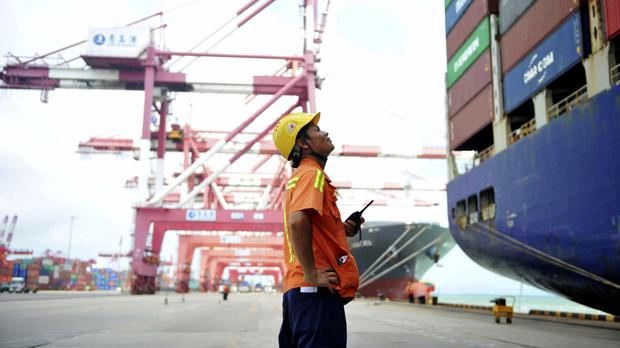 A worker watches as shipping containers are loaded onto a ship at a port in Qingdao in eastern China as the country's government responded to a trade probe ordered by Donald Trump (Chinatopix via AP)