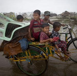 A Rohingya man pushes a rickshaw with children and belongings as he leaves a camp for displaced people in Burma (AP)