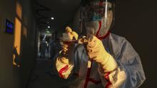 A medical worker in a protective suit writes on a tube after collecting a sample for nucleic acid tests from a suspected virus patient at a hotel being used to place people in medical isolation in Wuhan (Chinatopix via AP)