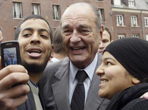 Jacques Chirac poses with residents during a visit to Amiens, northern France, in 1996 (Michel Spingler/AP)