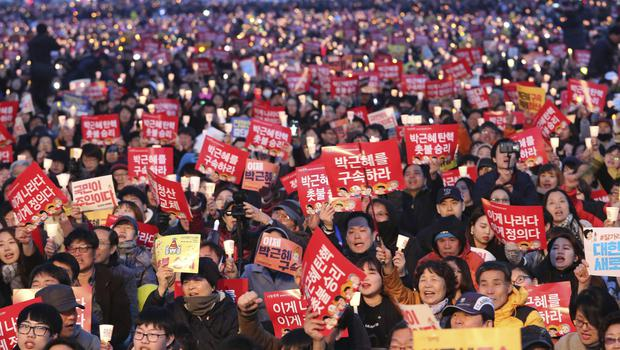 Protesters stage a candle-lit vigil calling for impeached president Park Geun-hye's arrest in Seoul (Ahn Young-joon/AP)