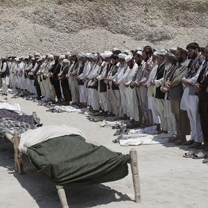 Afghan men offer funeral prayers in front of the bodies of seven civilians killed by a roadside bomb in the Alingar district of Laghman province