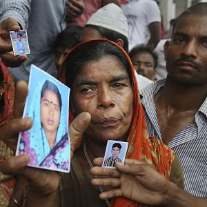 A Bangladeshi woman weeps as she holds a picture of a missing relative with others at the site of a building that collapsed in Savar (AP)