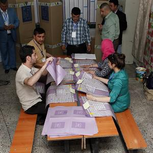 Election officials begin counting the results after the polls closed at the country's provincial elections in Baghdad, Iraq on Saturday (AP)