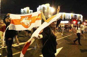 Protesters hold historical Belarusian flags as they gather after the election (Sergei Grits/AP)