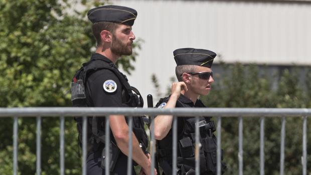 Police officers guard a road leading to a plant which was attacked on Friday in Saint-Quentin-Fallavier, southeast of Lyon (AP)