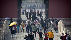 Visitors wearing face masks to protect against the new coronavirus walk through the Forbidden City (Mark Schiefelbein/AP)