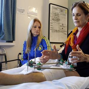 Beth Roche, right, whose left leg was severely injured by one of the marathon bombs sits on her bed with her daughter Rebecca at Spaulding Rehabilitation Hospital in Boston (AP)