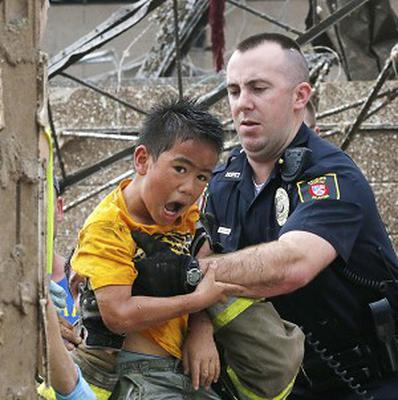 A boy is pulled from beneath a collapsed wall at the Plaza Towers Elementary School following a tornado (AP/Sue Ogrocki)