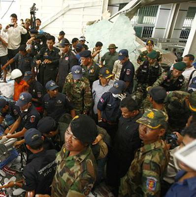 Cambodian rescuers at a factory that makes Asics sneakers, which has collapsed (AP)