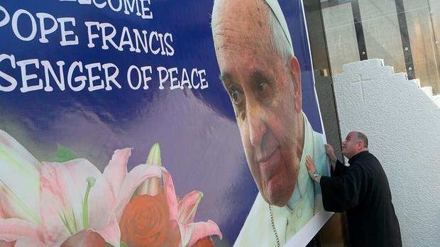 Father Nazeer Dako places a poster welcoming Pope Francis to St Joseph's Chaldean Church in preparation for the Pope's visit, in Baghdad, Iraq (AP)