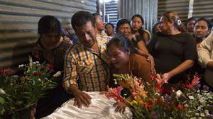 Maria Garcia, centre, cries during the wake for her 16-year-old daughter Siona Hernandez Garcia, who died in a youth shelter fire in Ciudad Peronia, Guatemala (Moises Castillo/AP)