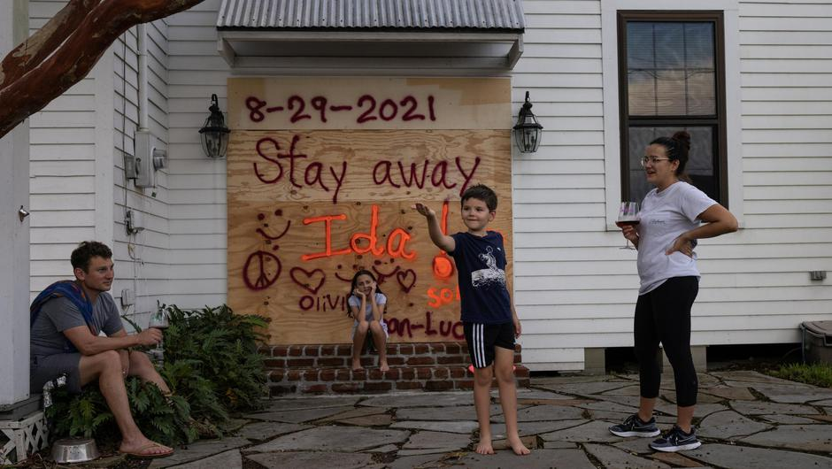 Jean-Luc Bourg, 8, catches a spider in front of his sister Olivia, 10, as his parents Jean Paul and Christina enjoy a glass of wine after boarding up their property in preparation for Hurricane Ida in Morgan City, Louisiana, US, August 28, 2021. Photo: REUTERS/Adrees Latif.