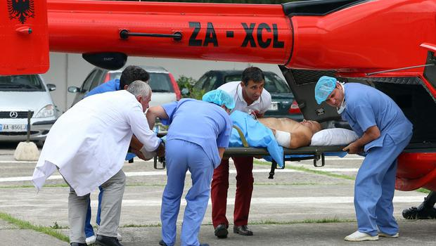 Medical staff carry a police officer out of a helicopter after he was injured in a shootout in the village of Lazarat. (AP)